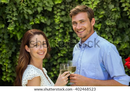 Portrait of happy couple toasting wineglasses at front yard - stock photo