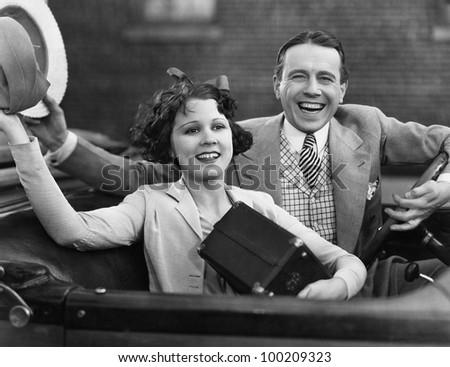 Portrait of happy couple waving in car - stock photo