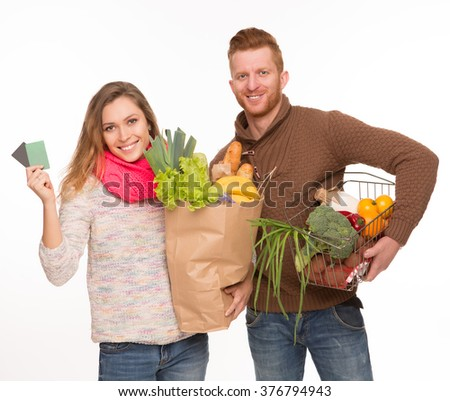 Portrait of happy couple with grocery shopping bags. Blond woman demonstrating credit cards over white background. - stock photo