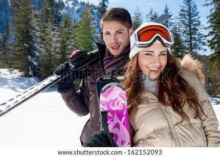 Portrait of happy couple with skis - stock photo