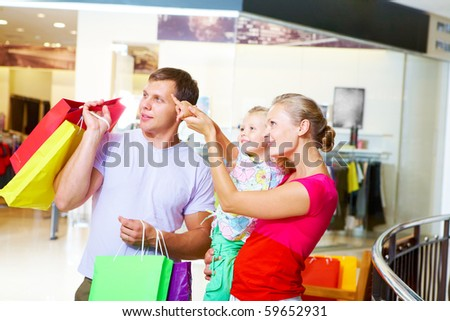 Portrait of happy couple with their daughter pointing at something in the mall - stock photo