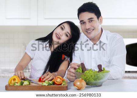 Portrait of happy couple with vegetables salad sitting in the kitchen while smiling at the camera - stock photo