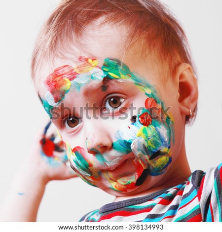 Portrait of happy cute little girl with colorful painted face - stock photo