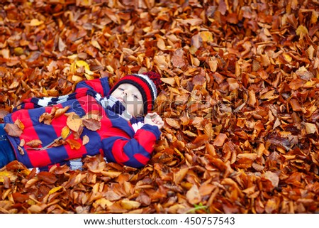 Portrait of happy cute little kid boy with autumn leaves background in colorful clothing. Funny child having fun in fall forest or park on cold day. With hat and scarf - stock photo