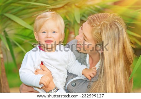 Portrait of happy cute mother with little baby in tropical park in sunny day, having fun outdoors, healthy lifestyle, love and childcare concept - stock photo