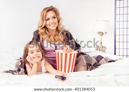 Portrait of happy daughter and mother watching cartoons with popcorn - stock photo