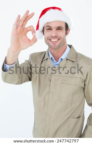 Portrait of happy delivery man in Santa hat gesturing OK sign against white background - stock photo