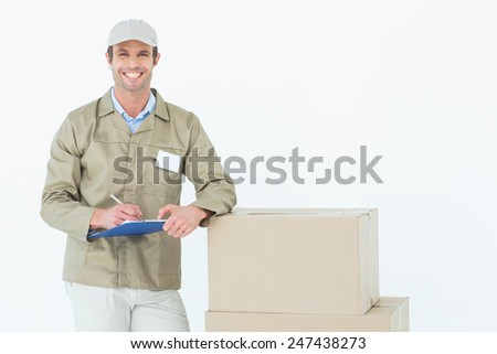 Portrait of happy delivery man writing on clipboard by cardboard boxes against white background - stock photo