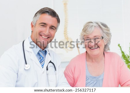 Portrait of happy doctor and female patient in clinic - stock photo