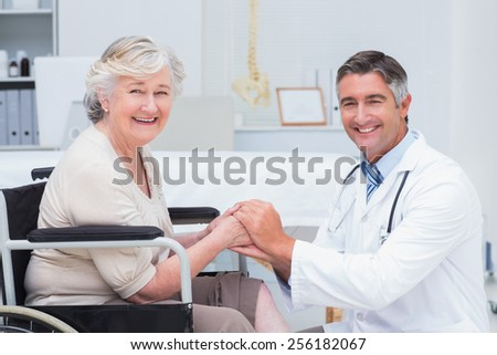 Portrait of happy doctor holding senior patients hands in clinic - stock photo