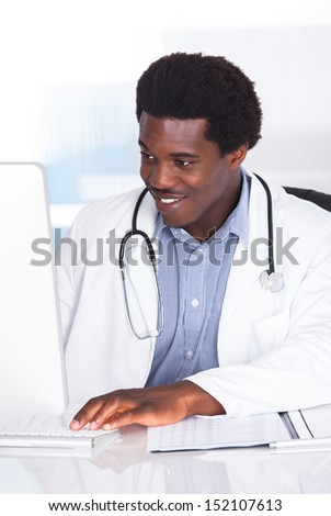 Portrait Of Happy Doctor With Stethoscope Sitting At A Desk - stock photo