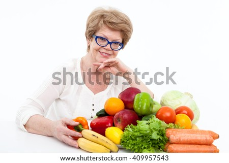 Portrait of happy elder Caucasian woman with fresh vegetables and fruits on table, white background - stock photo