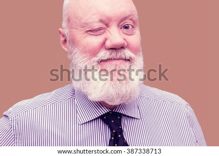 Portrait of happy elderly man posing on old-pink background, color and contrast manipulated - stock photo