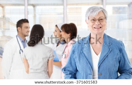 Portrait of happy elderly woman in glasses. Medical team in background. - stock photo