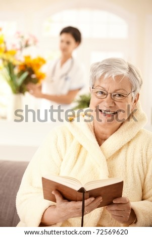 Portrait of happy elderly woman sitting on couch, reading book, nurse arranging flowers in background.? - stock photo