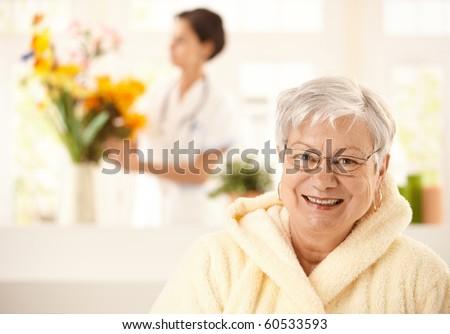 Portrait of happy elderly woman wearing bathrobe, nurse arranging flowers in background.? - stock photo