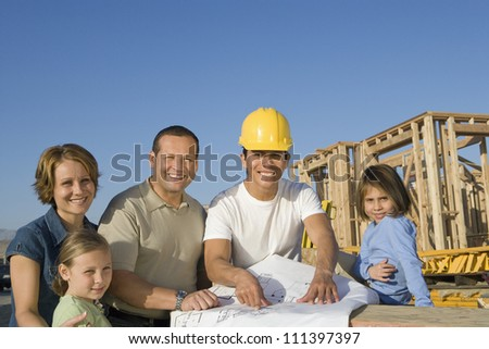 Portrait of happy family and male architect with blueprint at construction site - stock photo