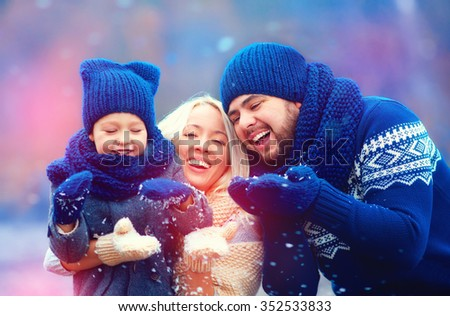 portrait of happy family blowing winter snow outdoors, holiday season - stock photo