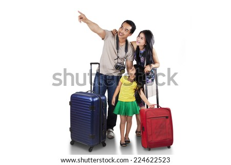 Portrait of happy family carrying suitcase for holiday and looking at copyspace - stock photo