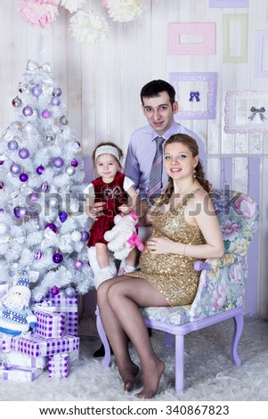 Portrait of happy family dad pregnant mom and daughter opening presents New Year eve - stock photo