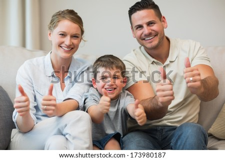 Portrait of happy family gesturing thumbs up while sitting on sofa at home - stock photo