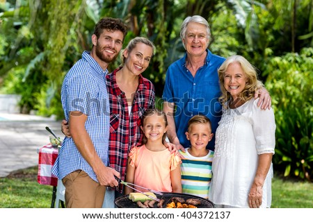 Portrait of happy family grilling food in barbeque at yard - stock photo