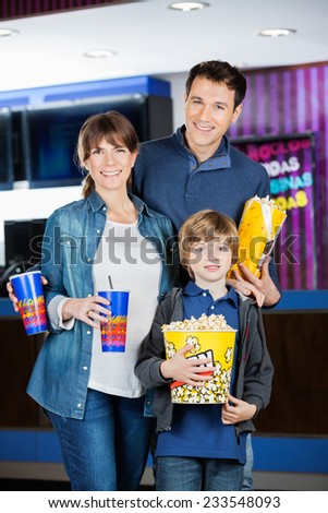 Portrait of happy family holding popcorns and drinks at cinema - stock photo