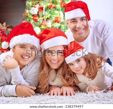 Portrait of happy family in Christmas eve at home, cheerful parents with two cute kids lying down on the floor near beautiful decorated Xmas tree  - stock photo