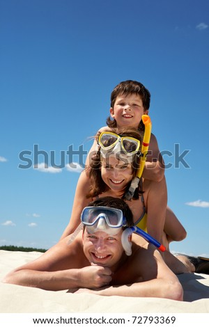 Portrait of happy family in goggles and flippers lying on sandy beach against blue sky - stock photo