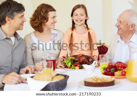 Portrait of happy family looking at joyful girl during Thanksgiving dinner - stock photo