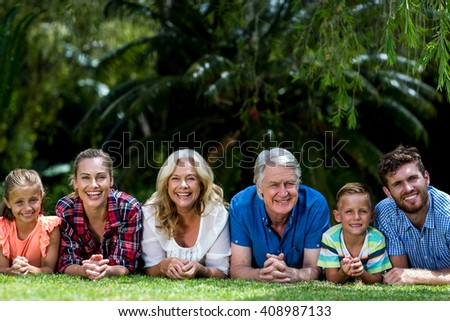 Portrait of happy family lying on grass at yard - stock photo