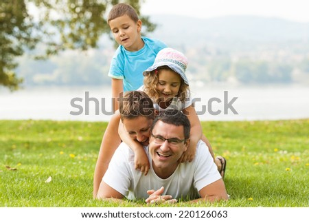 Portrait of happy family making a human pyramid in the meadow.  - stock photo