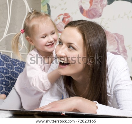 portrait of happy family, mother and daughter in bed reading book and talking, laughing - stock photo