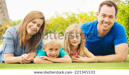 Portrait of Happy Family of Four Outside. Parents and Two Young Children - stock photo