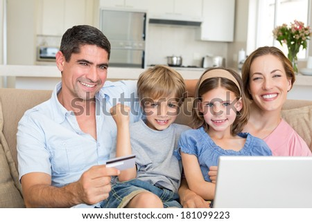 Portrait of happy family of four shopping online in house - stock photo