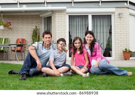 Portrait of happy family of four sitting in backyard of new home - stock photo