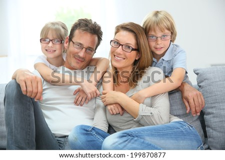 Portrait of happy family of four wearing eyeglasses - stock photo
