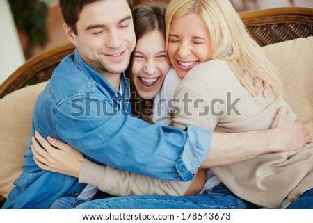 Portrait of happy family of three embracing  - stock photo