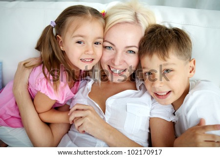Portrait of happy family of three looking at camera - stock photo