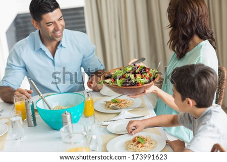 Portrait of happy family of three sitting at dining table in the home - stock photo