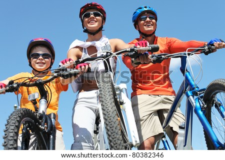 Portrait of happy family on bicycles against blue sky - stock photo