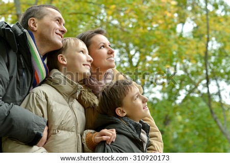 Portrait of happy family relaxing in autumn park - stock photo