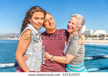 Portrait of happy family - Senior couple with their daughter on vacation - Grandfather and grandmother hugging their nephew outdoors - stock photo
