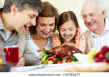 Portrait of happy family sitting at festive table and looking at roasted turkey - stock photo