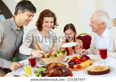 Portrait of happy family sitting at festive table while having Thanksgiving dinner - stock photo