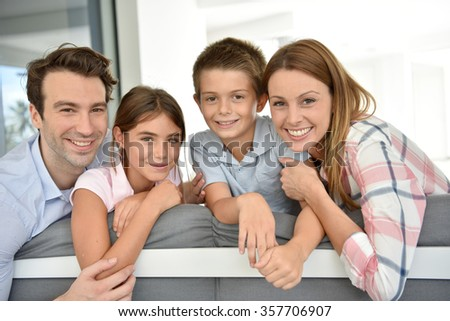 Portrait of happy family sitting in sofa - stock photo