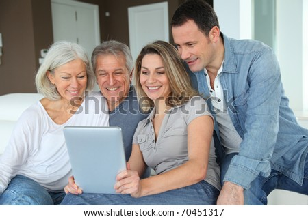 Portrait of happy family sitting in sofa with electronic tablet - stock photo