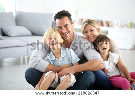 Portrait of happy family sitting on floor - stock photo