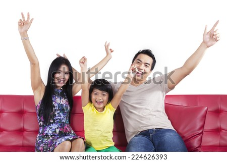 Portrait of happy family sitting on sofa and expressing freedom together - stock photo