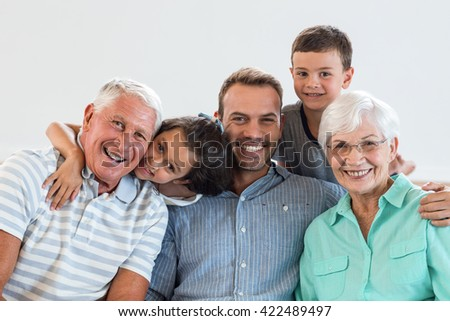 Portrait of happy family sitting on sofa and smiling in living room - stock photo